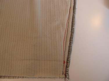 red stitching line takinjg in fabric so hem will lie flat on a tapered pant, 187