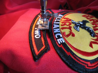 sewing on a patch on a karate uniform, 217