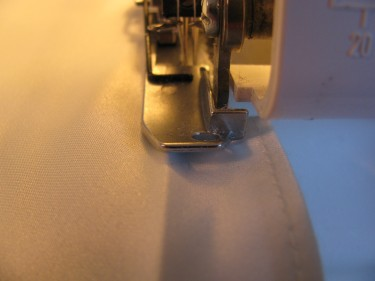 using a serger to trim off the edge of the partial hem, 688