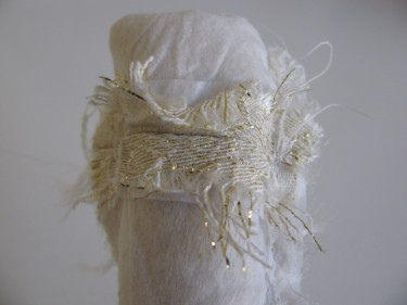 view of the wide strap turned inside out with frayed edges, white brocade