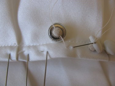 a close up of stitching a satin covered button on a wedding dress