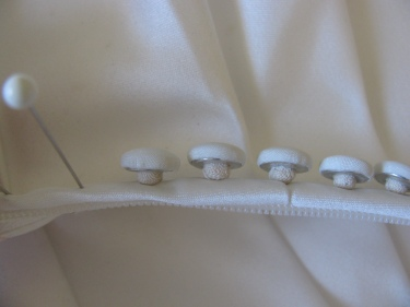 side view of the satin covered buttons lined up like mushrooms on the surface of the dress.