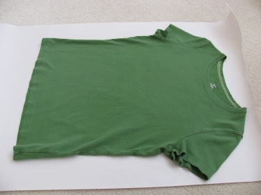 t-shirt laid out on newsprint to make a sewing pattern from it, 1354