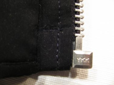 view of the very bottom of the zipper tab in my black jacket after the new zipper is in, sewing blog 1417