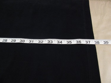 Measuring the black dress for the hem on the ironing board