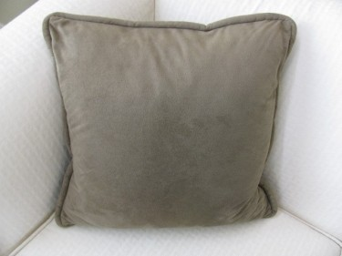 green pillow with piping